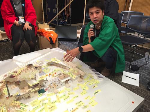 模型を指さし未来創造塾の設計プランを語る菊地さん