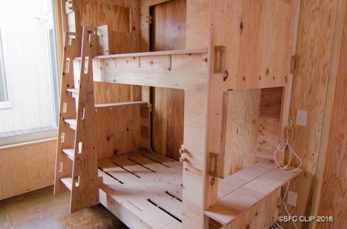 木製のベッド。側面にはハンガーをかける穴があいている