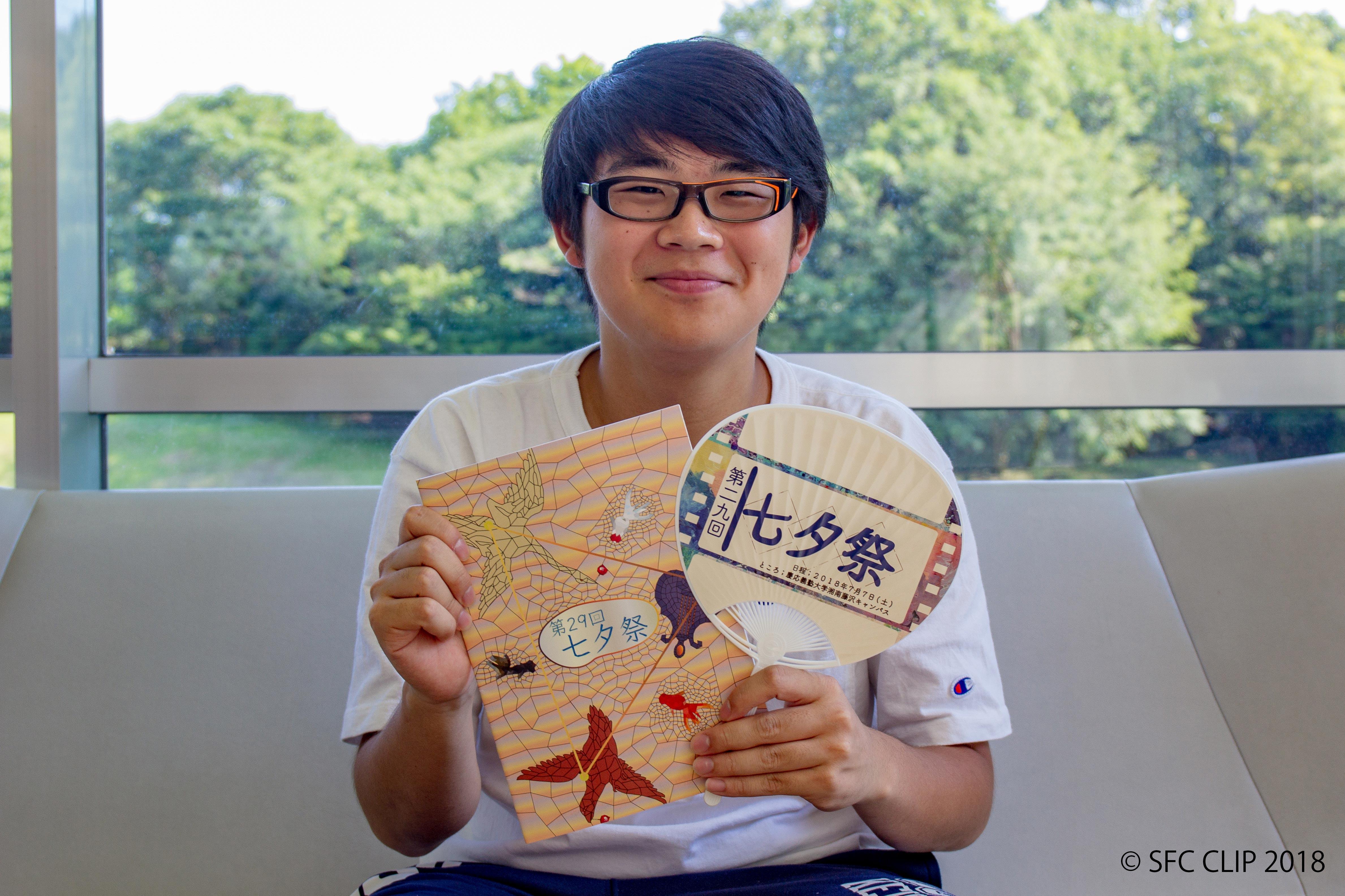 特製うちわとパンフレットを持って笑顔を見せる加藤さん