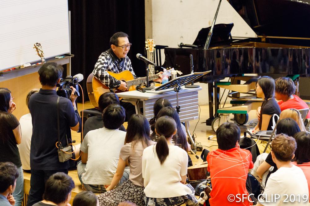 学生に囲まれて自身のうたを演奏
